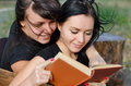Two close woman friends enjoying a book Royalty Free Stock Images