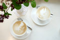 Two coffees on the white table Royalty Free Stock Photo
