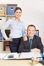 Two colleagues in company office smiling at the desk a Royalty Free Stock Images