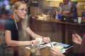 Two colleagues with tablets discussing work during lunch in the cafe Royalty Free Stock Photo