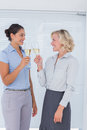 Two colleagues toasting with champagne at the office Stock Photos