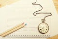 Two colored wooden pencils, notebook and old pocket watch Royalty Free Stock Photo