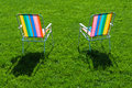 Two colorful chairs standing on grass Royalty Free Stock Photo