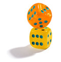 Two colorful dice balanceing on each other yelllow and orange balancing with the top one angled a white background conceptual of Stock Photos