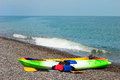 Two colorful sea kayaks with paddles and life jackets on stony b Royalty Free Stock Photo