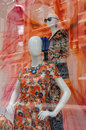 Two colourful mannequins bright colourful dresses shop window street scene reflecting glass Royalty Free Stock Photo