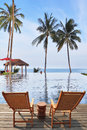 Two comfortable guest sun loungers and bedside table great review for a luxury beachfront pool the ocean swaying palm trees Royalty Free Stock Photography