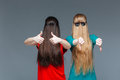 Two comical women with faces covered by long hair gesturing Royalty Free Stock Photo