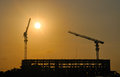 Two construction cranes at work against the evening sky Royalty Free Stock Photo