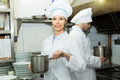 Two cooks at restaurant kitchen professional working Royalty Free Stock Photos