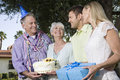 Two couples during a birthday party in garden young and senior with gift and cake the Royalty Free Stock Images