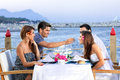 Two couples celebrating at the sea seated a table an open air waterfront restaurant enjoying glasses of cold white wine as Stock Photography