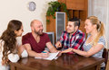 Two couples discussing and smiling terms of insurance company at apartment Stock Photos