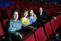 Two couples look at camera and laugh happy young in cinema theater focus on left pair Stock Photography