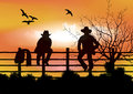 Two cowboys sitting on  fence Royalty Free Stock Photos