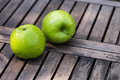 Two crisp green apples on a wooden table covered in small droplets of water slatted Stock Photo