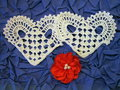 Two crochet hearts and red ribbon on blue background Royalty Free Stock Photography