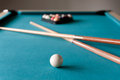 Two cue billiards lie on the table background of balls Royalty Free Stock Photo