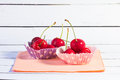 Two cupcake liners filled with cherries studio shot of on a paper napkin and white wood background Royalty Free Stock Photos