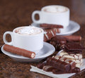 Two cups of coffee or hot cocoa with chocolates and cookies on brown background Stock Photos