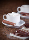 Two cups of coffee or hot cocoa with chocolates and cookies on brown background Royalty Free Stock Image