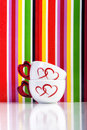 Two cups with hearts on colorful stripes background