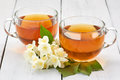 Two cups of jasmine tea and jasmine flowers on a white table Royalty Free Stock Photo