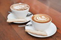 Two cups of latte art coffee in a white cup on wooden background Royalty Free Stock Image