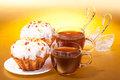 Two cups tea two muffins gold background Stock Photo