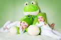 Two cute babies lying in frog hats with a soft toy Royalty Free Stock Photo