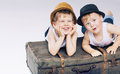 Two cute brothers lying on luggages suitcases Stock Images