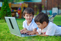 Two cute children is laying in grass on laptop Royalty Free Stock Photos