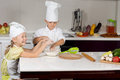 Two cute children making homemade pizza dressed in white chefs apron and hat working at the counter mixing ingredients for the Royalty Free Stock Photos
