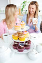 Two cute friends eating cupcakes in the kitchen Royalty Free Stock Image