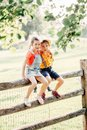Two cute funny Caucasian children boy girl sitting on wooden rustic fence in park outside. Friends siblings kids hugging Royalty Free Stock Photo