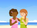 Two cute girls enjoying ice cream on sunny beach Royalty Free Stock Images