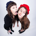 Two cute girls having fun and making funny faces on light blue background Royalty Free Stock Images