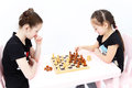 Two cute girls play chess black rook move in studio Stock Photos