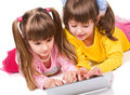 Two cute girls playing on laptop Stock Photography