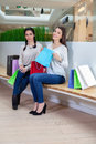 Two cute girls are sitting on a bench in the mall with gift bags . Royalty Free Stock Photo