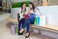 Two cute girls are sitting on a bench in the mall with gift bags. Royalty Free Stock Photo