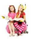 Two cute little exited girls sitting on suitcase with map preparing to travel deciding destinations wearing snorkel and mask Stock Photo