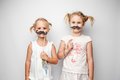 Two cute little girls with paper mustaches while posing against white background. Royalty Free Stock Photo