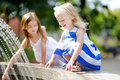 Two cute little girls playing with a city fountain on hot summer day Royalty Free Stock Photo