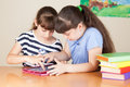 Two cute little school girls with tablet and colourful books Stock Photos