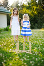 Two cute little sisters playing ring toss game outdoors on beautiful summer day Stock Images