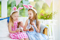 Two cute little sisters wearing bunny ears eating chocolate Easter rabbits. Kids playing egg hunt on Easter.