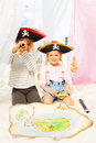 Two cute pirates looking through a toy spyglass Royalty Free Stock Photo