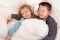 Two cute young children sleeping in bed together sharing the same with a little boy protectively cuddling his younger sister Royalty Free Stock Photography
