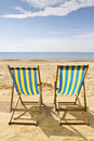 Two deck chairs on the beach Stock Images